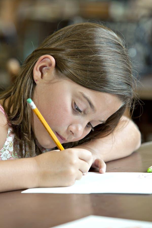 Nettes Schreiben des kleinen Mädchens mit Bleistift und Papier lizenzfreies stockfoto