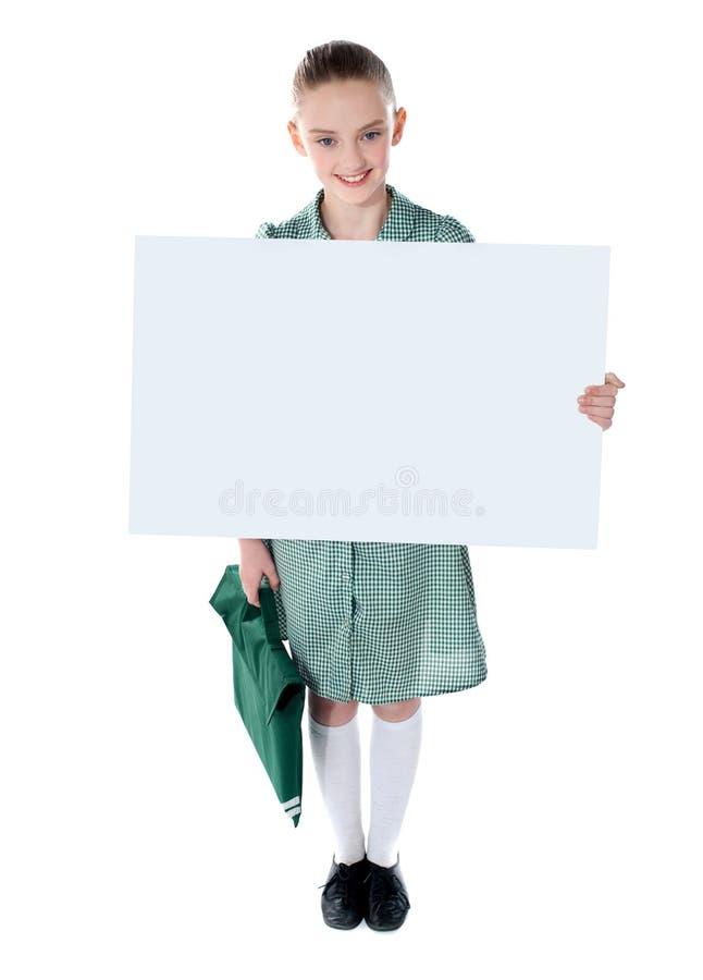Nettes Schulemädchen mit einem bekanntmachenden Vorstand stockfoto