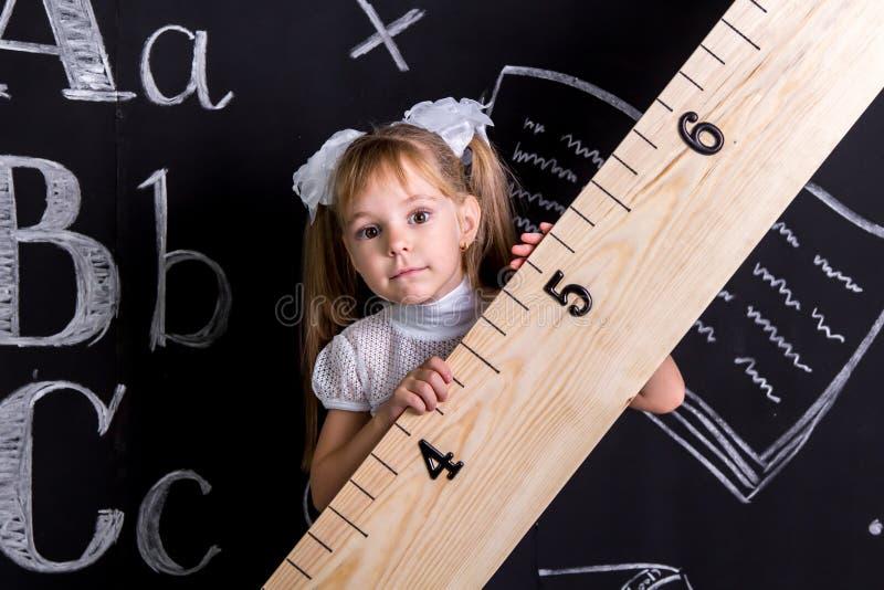 Nettes Schulmädchen, das vor der Tafel als Hintergrund diagonal hält den enormen Machthaber steht lizenzfreies stockbild
