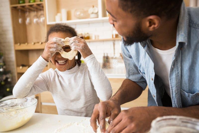Nettes schwarzes Mädchen, das Gebäck kocht und Spaß mit Vati hat stockfotografie