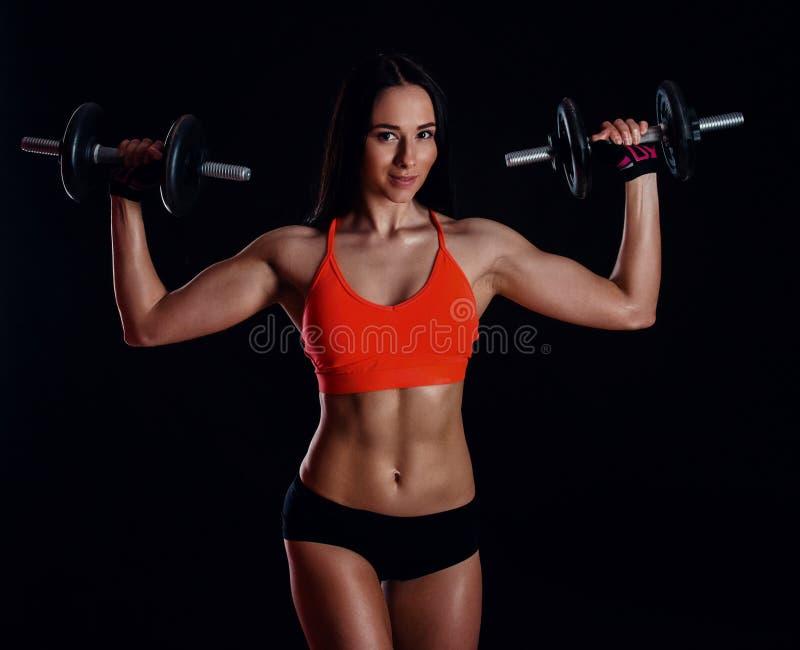 Nettes sexy Mädchen, das Training mit den Dummköpfen lokalisiert über schwarzem Hintergrund tut Athletische junge Frau tun ein Ei stockfotos