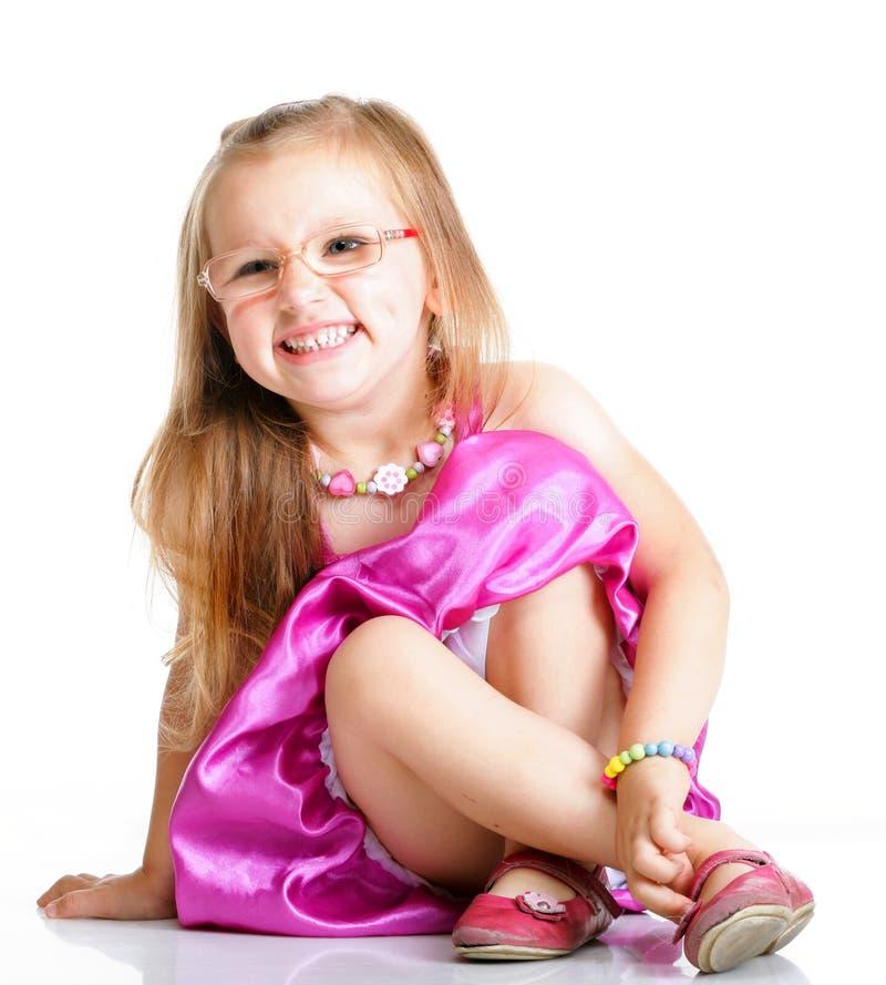 Nettes Sitzen des kleinen Mädchens und Lächeln, lokalisiert stockfoto