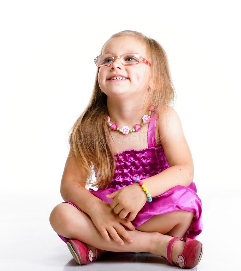 Nettes Sitzen des kleinen Mädchens und Lächeln, lokalisiert stockfotos