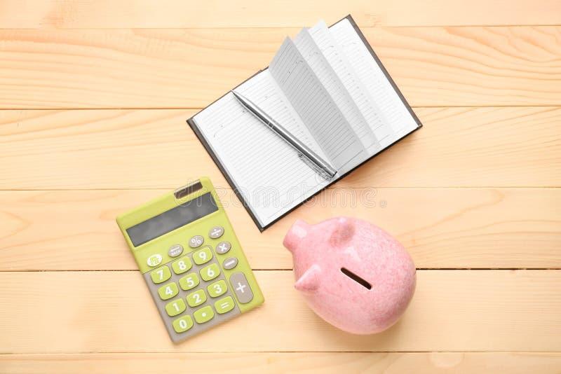 Nettes Sparschwein mit Notizbuch und Taschenrechner auf Holztisch lizenzfreie stockfotos