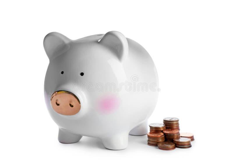 Nettes Sparschwein und Münzen auf Weiß Banknoten mit schwarzem Rechner stockfoto