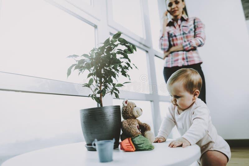 Nettes spielendes Baby, während junge Mutter telefoniert stockbild