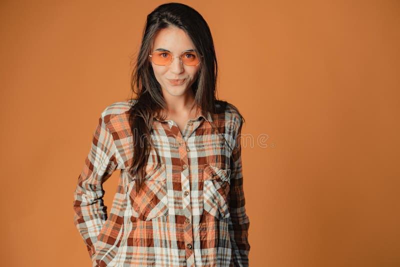 Nettes spielerisches junges brunette Mädchen, das Gesichter auf orange Hintergrund macht stockfoto