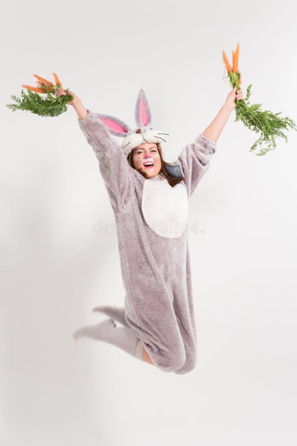 Nettes springendes Häschenmädchen mit Karotten stockbilder