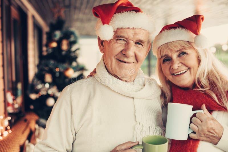 Nettes streifend älteres Paar, das zusammen Weihnachten feiert lizenzfreie stockfotos