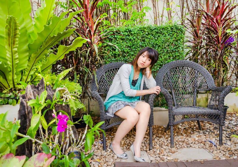Nettes thailändisches Mädchen ist das Sitzen einsam auf dem Stuhl stockbild