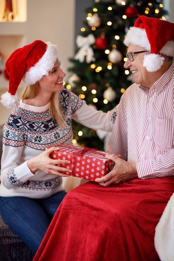 Nettes Tochterausgabe Weihnachten mit älterem Vater lizenzfreie stockfotografie