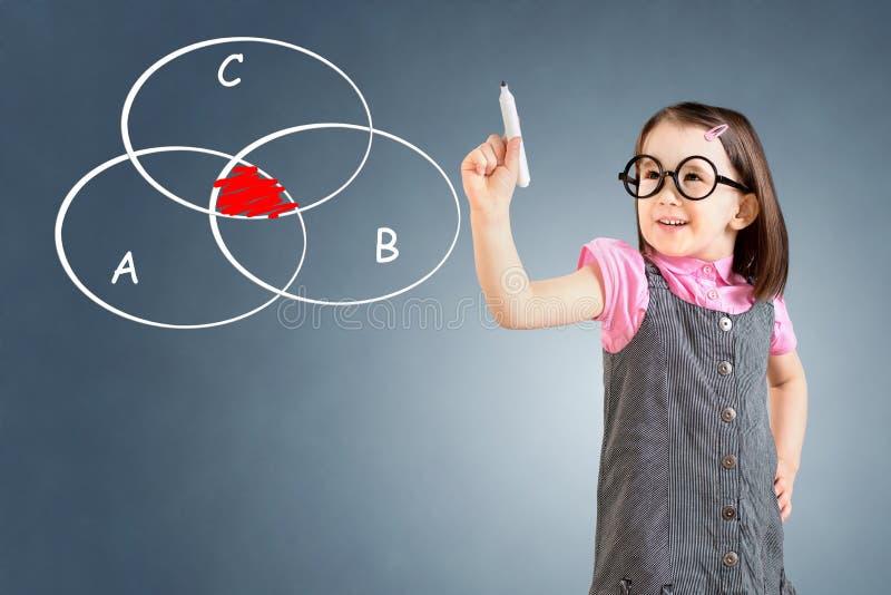 Nettes tragendes Geschäftskleid des kleinen Mädchens und zeichnendes geschnittenes Kreisdiagramm auf whiteboard Hintergrund für e lizenzfreies stockbild
