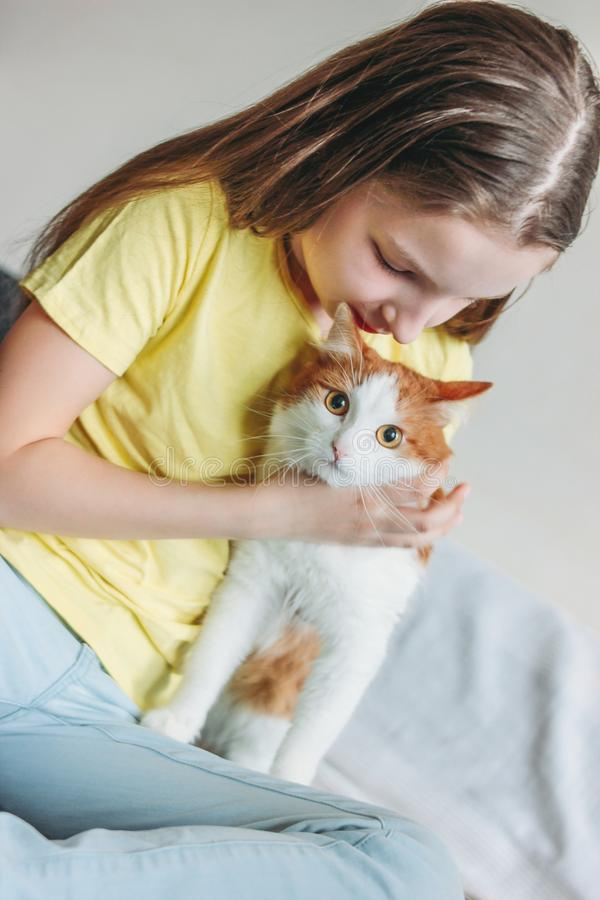 Nettes Tweenmädchen im gelben T-Shirt mit ihrer weißen Katze zu Hause lizenzfreie stockbilder