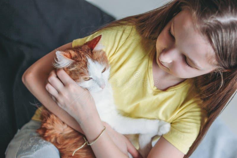 Nettes Tweenmädchen im gelben T-Shirt mit ihrer weißen Katze zu Hause stockfotos