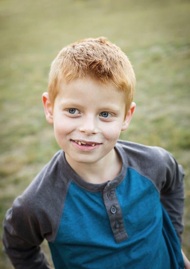 Nettes und dummes kleines rotes behaartes Jungenporträt draußen stockfoto