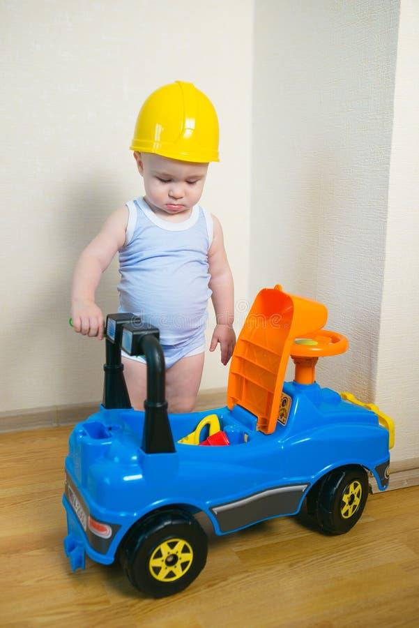 Nettes und ernstes Baby, das zuhause ein Spielzeugauto repariert stockfotos