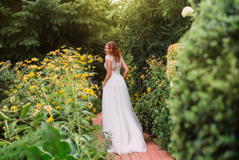 Nettes und nettes Mädchen in einem langen Kleid der weißen eleganten Hochzeit mit einem Zug und in einem transparenten Gewebe mit stockfotografie