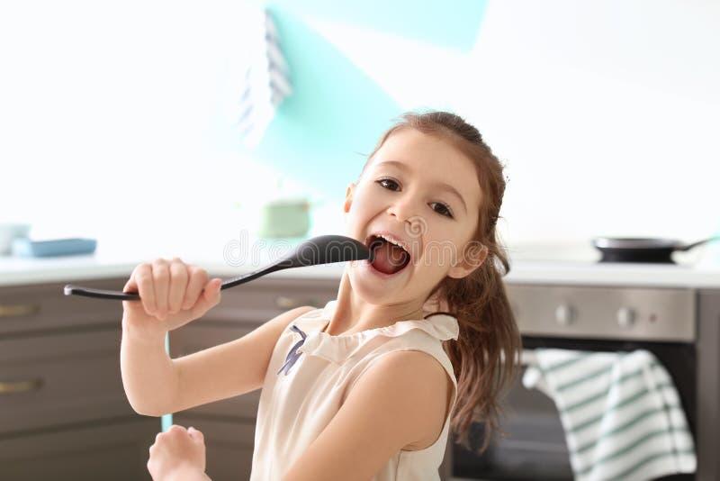 Nettes unterzeichnendes Lied des kleinen Mädchens in Löffel stockbild
