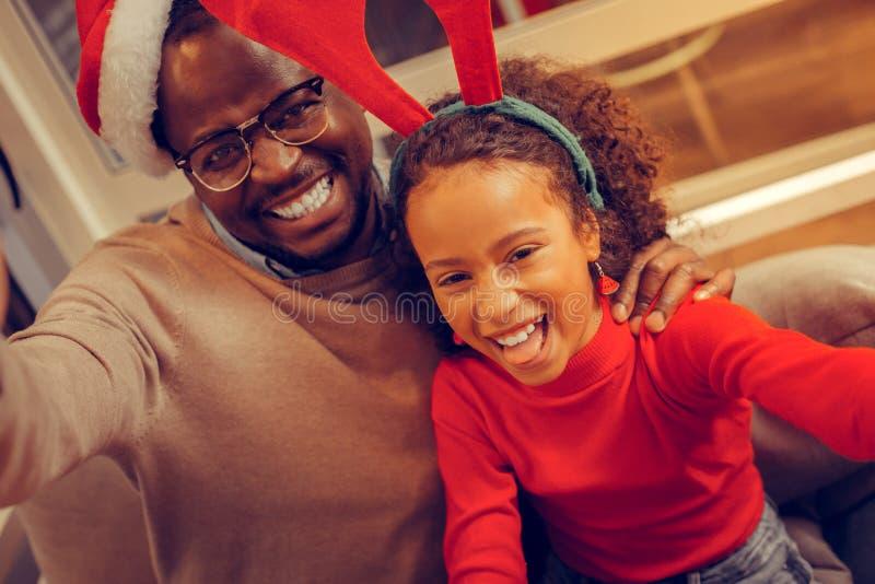 Nettes Vater- und Tochtergefühl aufgeregt, Weihnachten feiernd stockfotografie