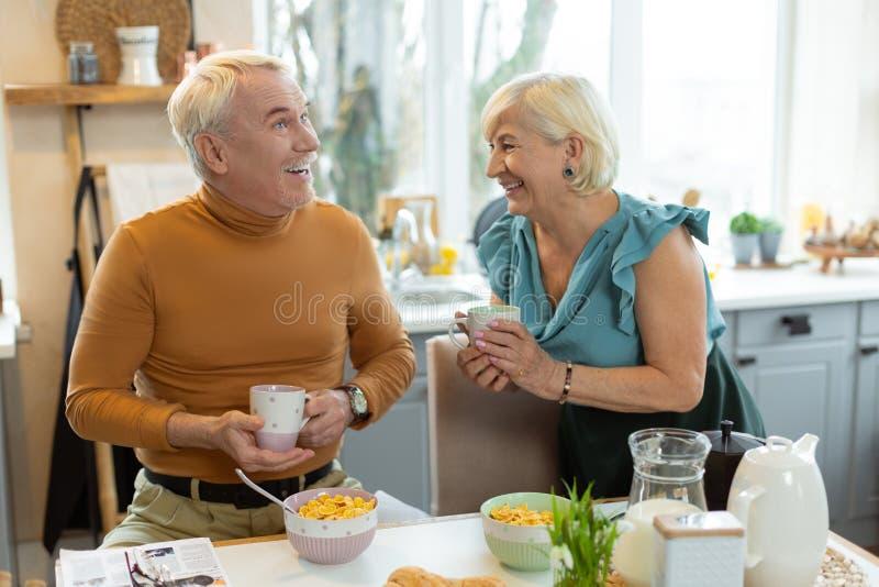 Nettes verheiratetes Paar, das ein Lachen beim Frühstücken teilt lizenzfreie stockfotos