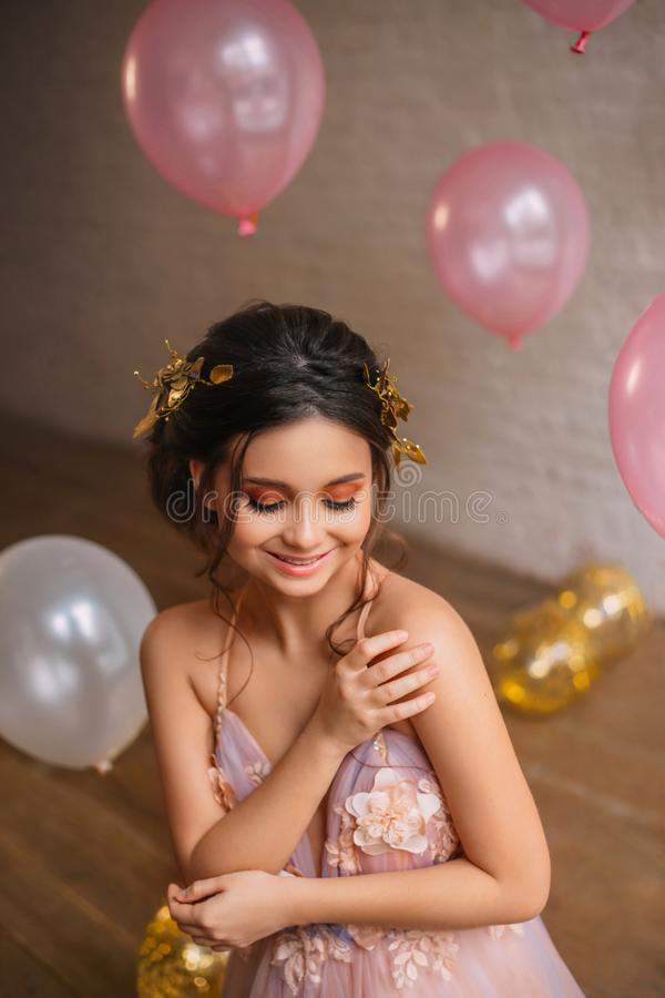 Nettes verlegenes bescheidenes zierliches Mädchen mit dem dunklen Haar und einer Goldkante sitzt in einem herrlichen rosa Pfirsic stockfotos