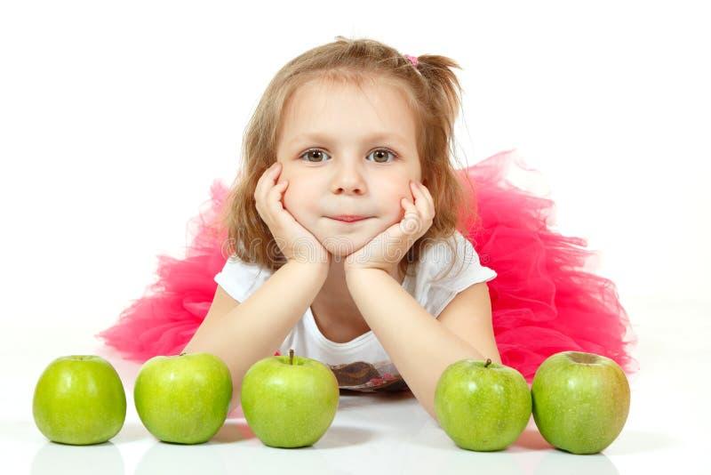 Nettes wenig Mädchen Lügen und playng mit Äpfeln lizenzfreie stockfotografie