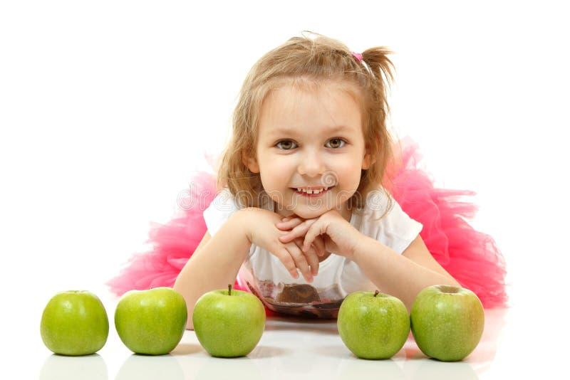 Nettes wenig Mädchen Lügen und playng mit Äpfeln lizenzfreie stockbilder
