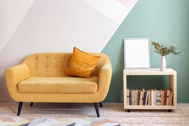 Nettes Wohnzimmer mit Couch, Teppich, Grünpflanze auf einem Bücherschrank stockfoto