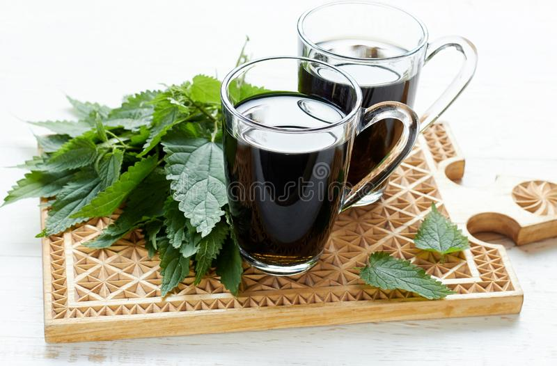 Nettle tea or decoction in glass cups, fresh herbal leaves on wooden cutting board stock image