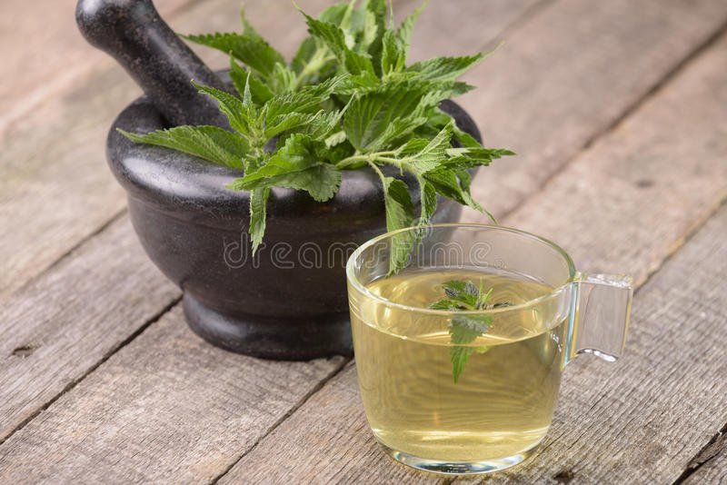 Nettle tea in a glass coup. Nettle tea in a glass cup on wooden surface stock photography