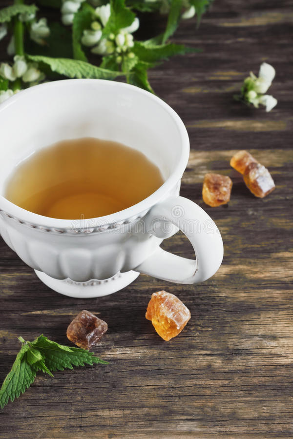 Nettle tea. And twigs of fresh nettle on the old wooden background. health and diet beverage stock photography