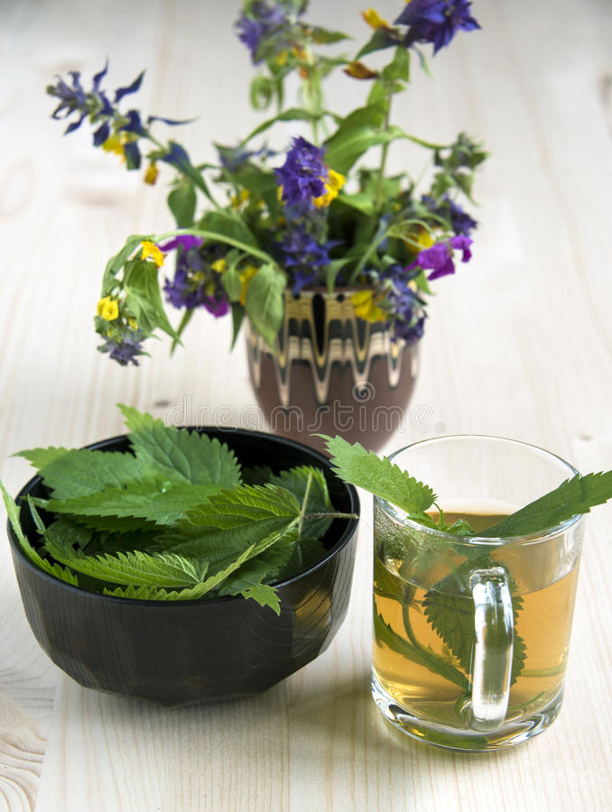 Nettle tea and wild flowers. Nettle tea on the wood background leaves in the cup and nettle in a bowl royalty free stock photography