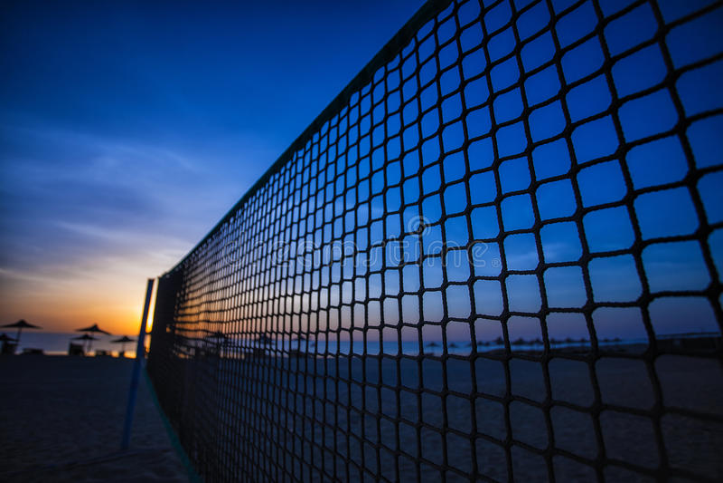 Netto volleyball en zonsopgang op het strand stock foto's