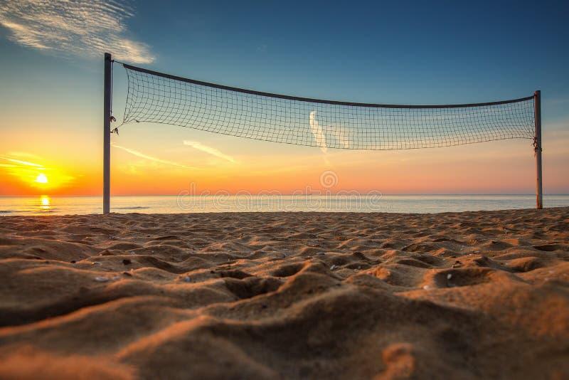 Netto volleyball en zonsopgang op het strand stock foto