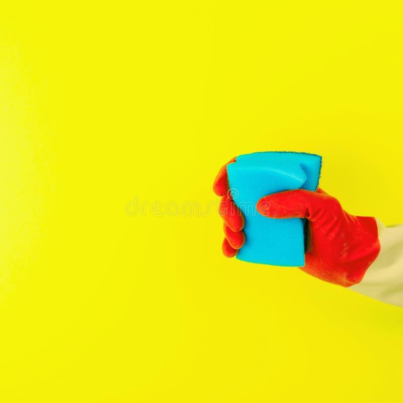 Nettoyage avec les gants et l'éponge en caoutchouc rouges photos stock