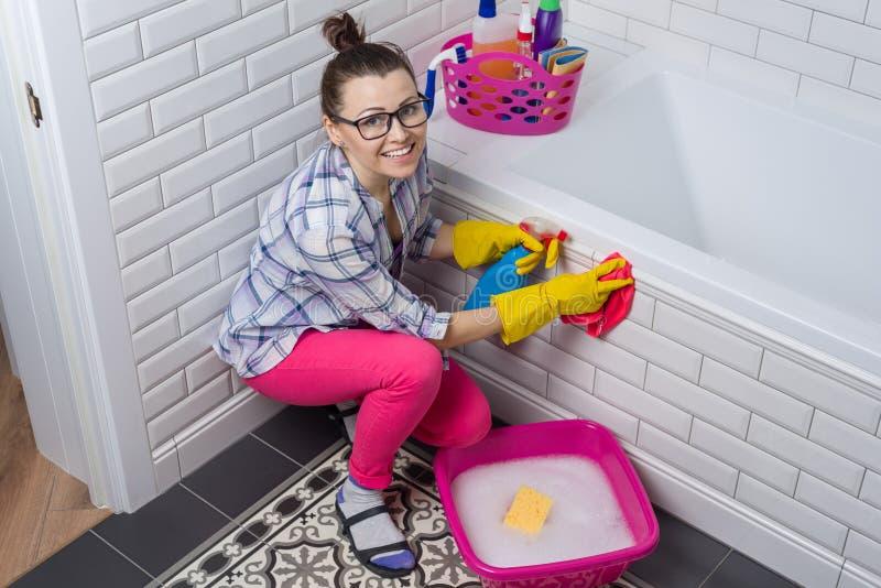Nettoyage de Chambre La femme nettoie dans la salle de bains à la maison image stock