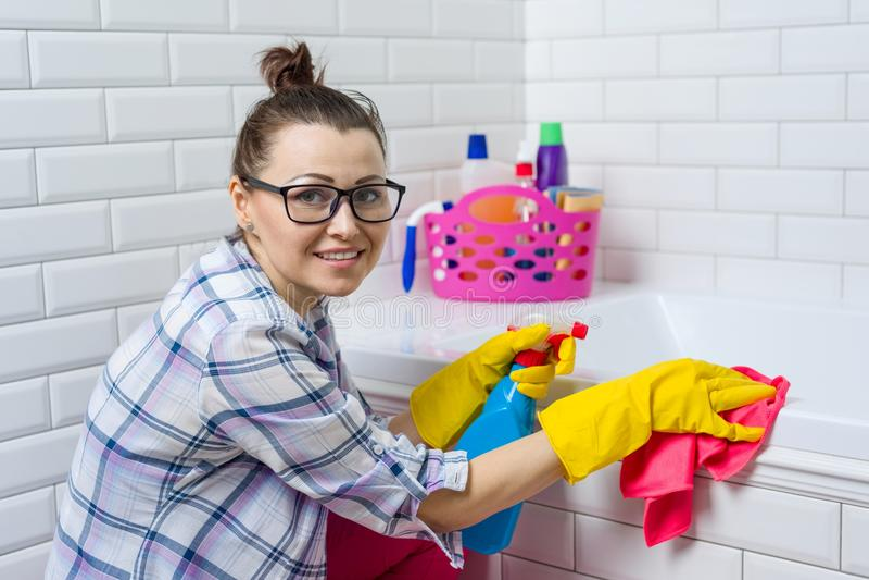 Nettoyage de Chambre La femme nettoie dans la salle de bains à la maison photos stock