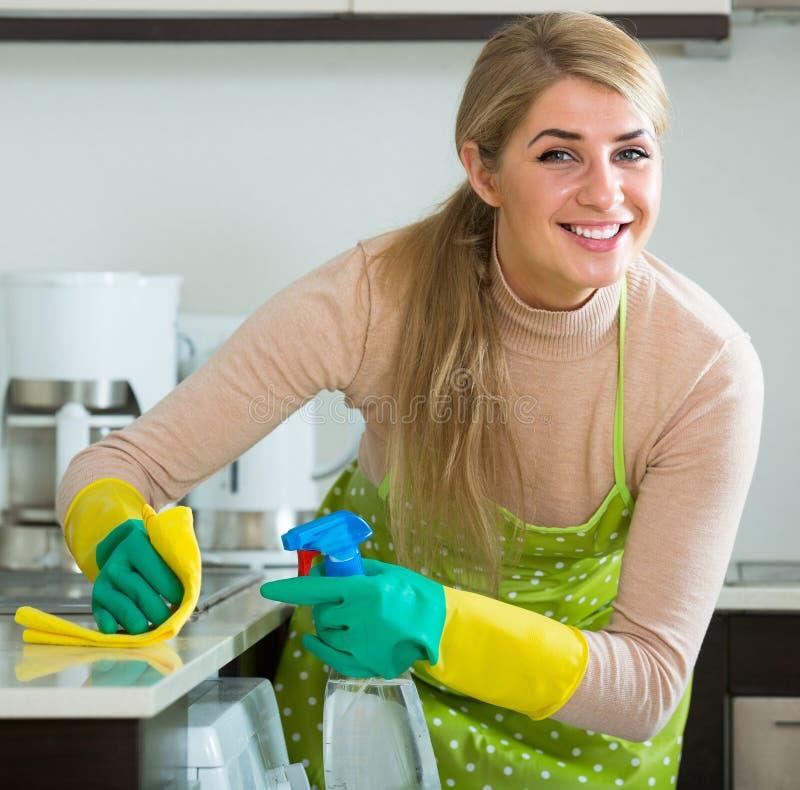 Nettoyage de femme au foyer dans la cuisine à la maison photos stock