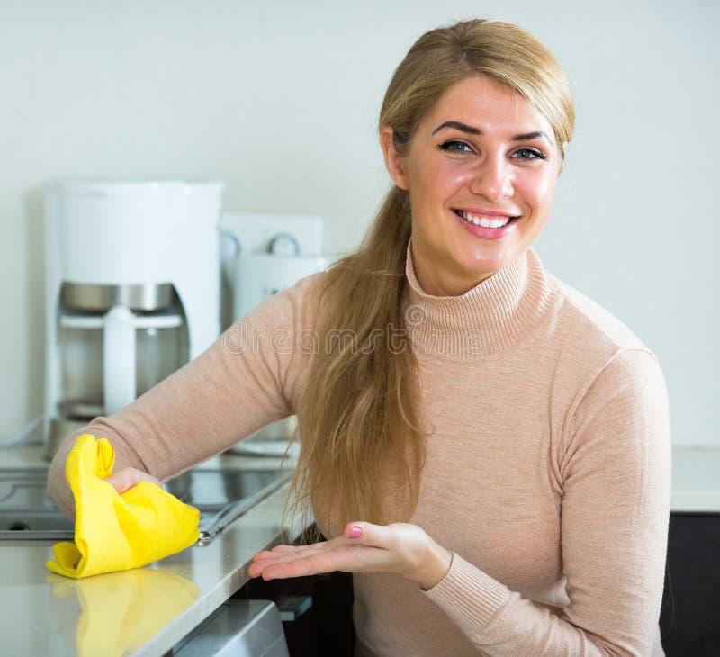 Nettoyage de femme au foyer dans la cuisine à la maison photographie stock