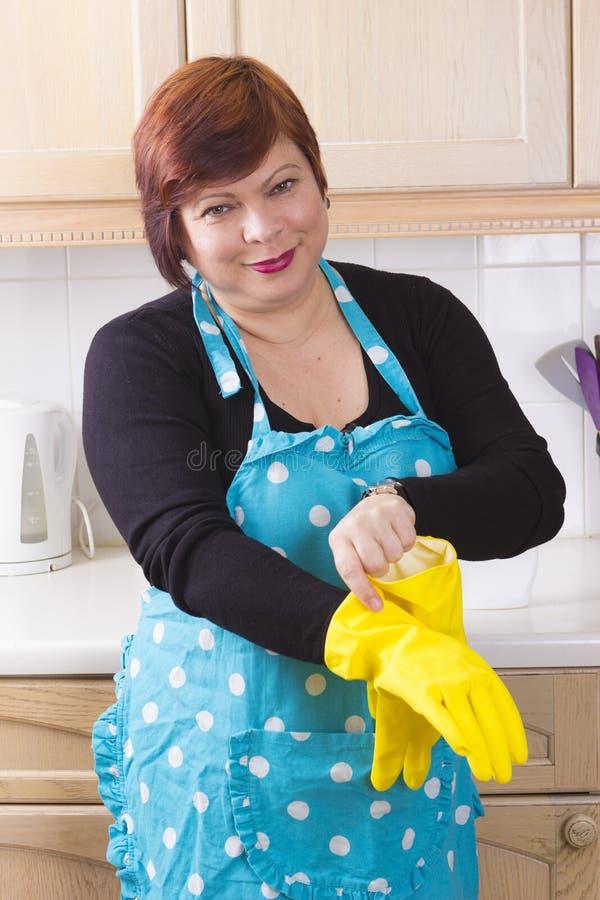 Nettoyage de femme de Moyen Âge dans la cuisine photographie stock libre de droits