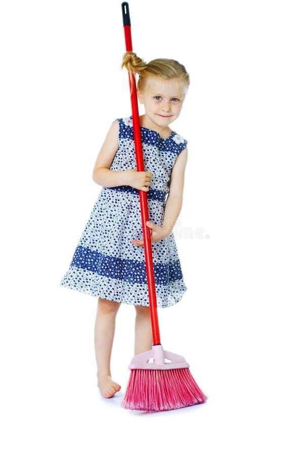Nettoyage de petite fille avec le balai images stock