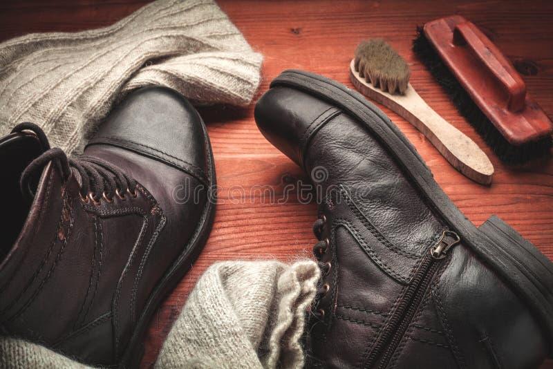 Nettoyage des bottes des hommes photos stock