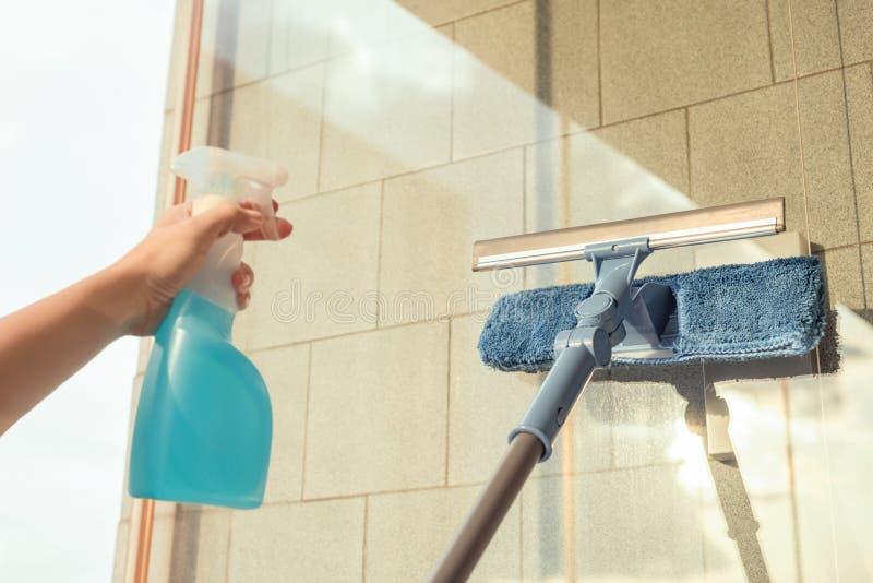 Nettoyage des filles Fenêtre de balcon par pulvérisation Produits de nettoyage et essuie avec la serpillière Éponge au coucher du photographie stock