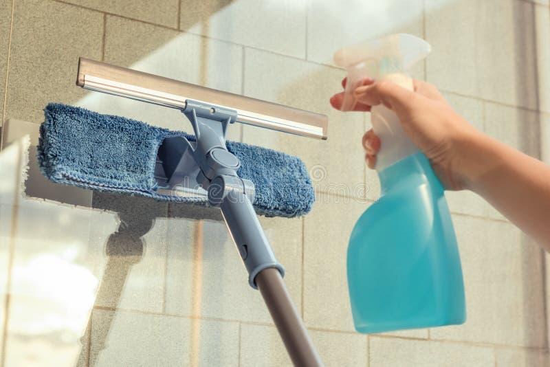 Nettoyage des filles Fenêtre de balcon par pulvérisation Produits de nettoyage et essuie avec la serpillière Éponge au coucher du photo libre de droits