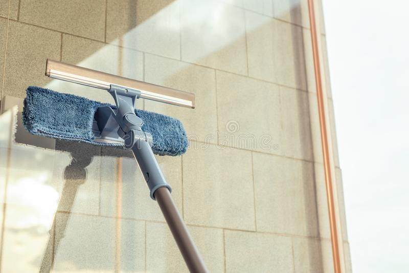 Nettoyage des filles Fenêtre de balcon par pulvérisation Produits de nettoyage et essuie avec la serpillière Éponge au coucher du images libres de droits