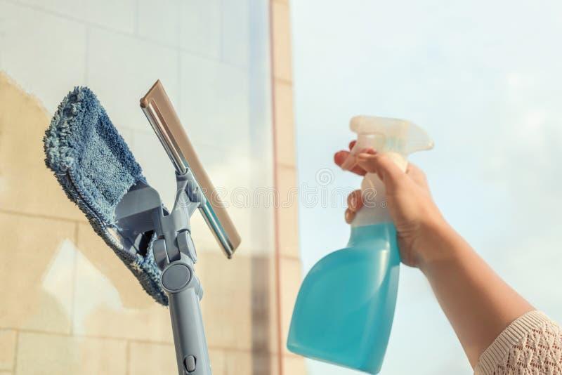 Nettoyage des filles Fenêtre de balcon par pulvérisation Produits de nettoyage et essuie avec la serpillière Éponge au coucher du image stock