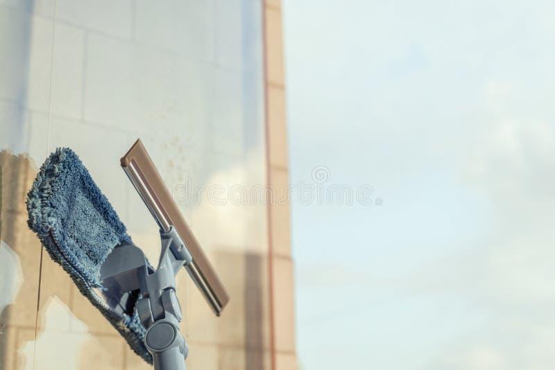 Nettoyage des filles Fenêtre de balcon par pulvérisation Produits de nettoyage et essuie avec la serpillière Éponge au coucher du photo stock