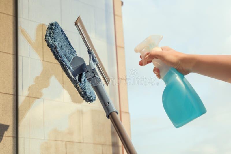 Nettoyage des filles Fenêtre de balcon par pulvérisation Produits de nettoyage et essuie avec la serpillière Éponge au coucher du photographie stock libre de droits