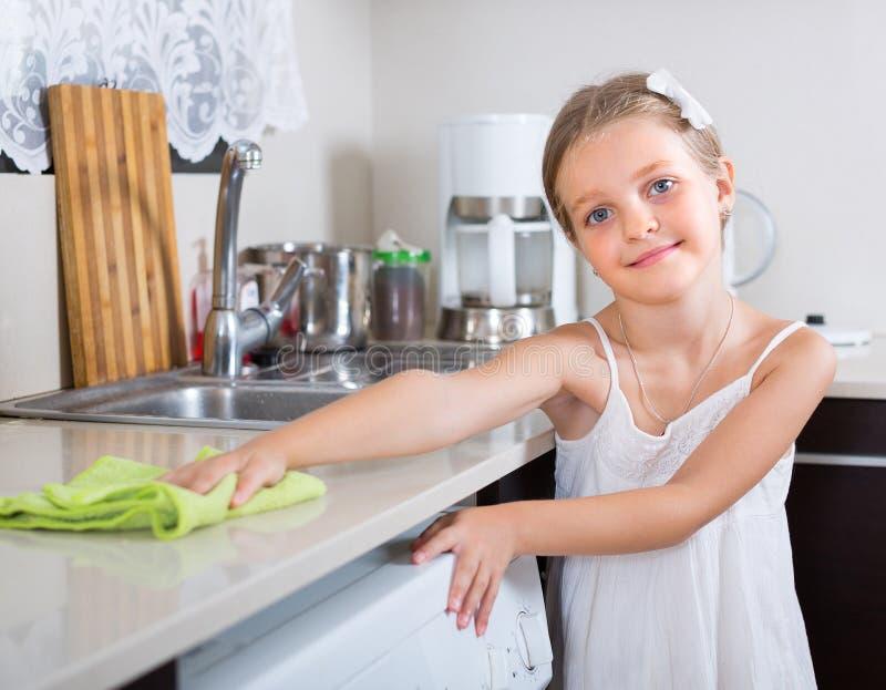 Nettoyage mignon de petite fille à la cuisine photo stock