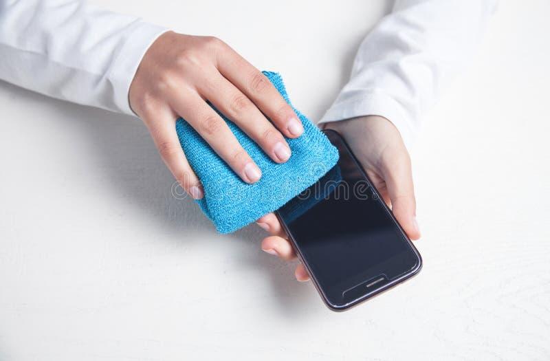 Nettoyer le smartphone au bureau photo libre de droits